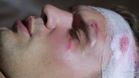 Uomo con le lesioni alla testa che si trovano sul letto Testa bendata contusione sul suo fronte archivi video