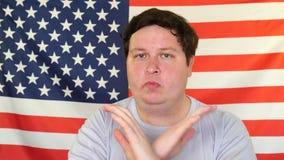 Uomo con le mani attraversate che mostrano gesto di arresto sui precedenti di una bandiera di U.S.A. archivi video
