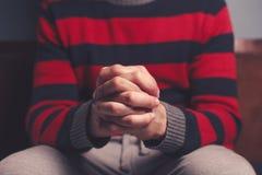 Uomo con le mani piegate nella preghiera Fotografia Stock