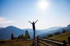 Uomo con le mani su sopra le montagne con cielo blu Immagini Stock Libere da Diritti