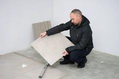 Uomo con le nuove piastrelle per pavimento immagine stock libera da diritti