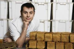 Uomo con le pagnotte di pane fresco in deposito Immagini Stock