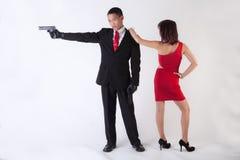 Uomo con le pistole e la donna attraente Immagini Stock Libere da Diritti