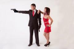 Uomo con le pistole e la donna attraente Immagini Stock