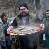 Uomo con le salsiccie della trippa Immagini Stock