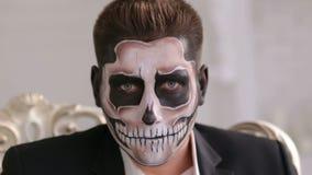 Uomo con lo scheletro di trucco che si siede nella vecchia sedia grigia Tema di orrore o di Halloween video d archivio