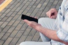 Uomo con lo smartphone sulla piattaforma immagini stock