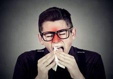 Uomo con lo starnuto freddo nel tessuto Fotografie Stock
