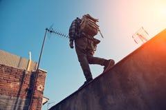 Uomo con lo zaino che cammina sopra l'alta parete sul bordo, sul tetto Fotografia Stock Libera da Diritti