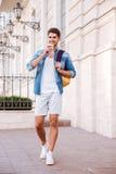 Uomo con lo zaino che cammina sulla via e sul caffè bevente Immagini Stock Libere da Diritti