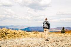 Uomo con lo zaino che fa un'escursione in primavera Fotografie Stock