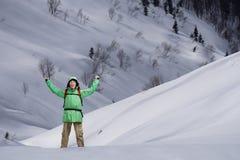 Uomo con lo zaino che sta sul pendio di montagna nevoso Viandante della montagna o dell'alpinista Fotografie Stock Libere da Diritti