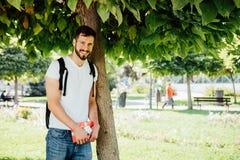 Uomo con lo zaino e un regalo accanto ad un albero immagine stock libera da diritti