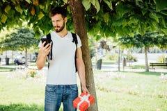Uomo con lo zaino e un regalo accanto ad un albero fotografia stock