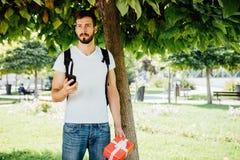 Uomo con lo zaino e un regalo accanto ad un albero immagini stock libere da diritti