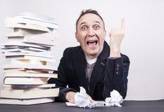 Uomo con molti libri sullo scrittorio che ha idea pazza circa scrittura Immagine Stock Libera da Diritti