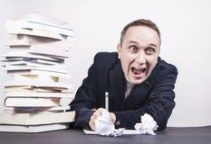 Uomo con molti libri sullo scrittorio che ha idea pazza circa scrittura Fotografia Stock
