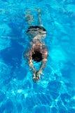 Uomo con nuoto del costume da bagno su uno stagno di acqua blu Immagine Stock Libera da Diritti