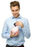 Uomo con piggybank e la carta di credito Fotografia Stock