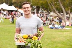 Uomo con prodotti freschi comprati al mercato all'aperto degli agricoltori Fotografia Stock