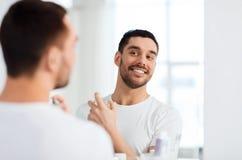 Uomo con profumo che esamina allo specchio il bagno Fotografie Stock Libere da Diritti