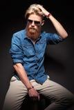 Uomo con seduta e la riparazione rosse lunghe della barba i suoi capelli Fotografia Stock
