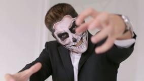 Uomo con terrificante di scheletro di trucco esaminando la macchina fotografica ed allungamenti le sue mani stock footage