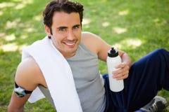 Uomo con un asciugamano sulla sua spalla che sembra tenuta ascendente uno sport immagini stock