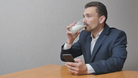 Uomo con un bicchiere di latte online con il telefono archivi video