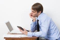 Uomo con un calcolatore al suo scrittorio nell'ufficio Fotografia Stock Libera da Diritti