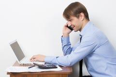 Uomo con un calcolatore al suo scrittorio nell'ufficio Immagini Stock Libere da Diritti