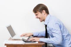 Uomo con un calcolatore al suo scrittorio nell'ufficio Immagine Stock Libera da Diritti