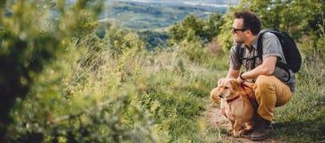 Uomo con un cane che riposa alla traccia di escursione Fotografia Stock Libera da Diritti