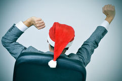 Uomo con un cappello di Santa che allunga i suoi braccioli nella sua sedia dell'ufficio Fotografie Stock Libere da Diritti