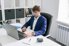 Uomo con un computer portatile nell'ufficio Immagine Stock