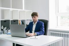 Uomo con un computer portatile nell'ufficio Fotografia Stock Libera da Diritti
