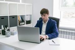 Uomo con un computer portatile nell'ufficio Fotografia Stock