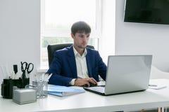 Uomo con un computer portatile nell'ufficio Fotografie Stock