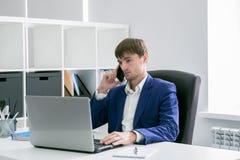 Uomo con un computer portatile nell'ufficio Immagini Stock Libere da Diritti