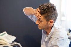 Uomo con un'emicrania davanti al computer immagine stock libera da diritti