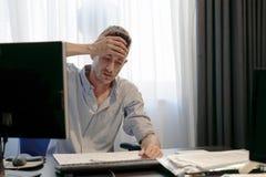 Uomo con un'emicrania davanti al computer fotografia stock libera da diritti