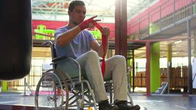 Uomo con un'inabilità in nastri di una cassa di aspirazione della sedia a rotelle sulle sue mani Mo lento archivi video