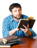 Uomo con un libro in sue mani alla tabella Fotografie Stock Libere da Diritti