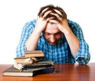 Uomo con un libro in sue mani alla tabella Immagini Stock