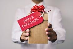 Uomo con un regalo con il Buon Natale del testo Fotografie Stock Libere da Diritti