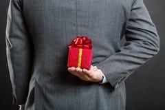 Uomo con un regalo dietro il suo indietro immagine stock libera da diritti
