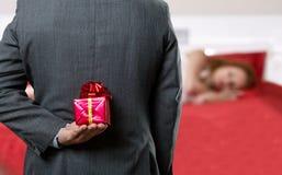 Uomo con un regalo dietro il suo indietro immagini stock