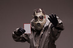 Uomo con un vestito da portare del hazmat della maschera antigas, tenente immagini stock