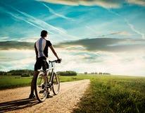Uomo con una bici sul bello fondo della natura Immagini Stock
