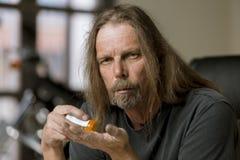 Uomo con una bottiglia di pillola di prescrizione dell'oppioide Immagine Stock